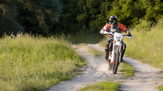 Stijlvolle man rijden motor in het bos