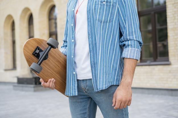 Stijlvolle man skater met longboard, lopend op straat