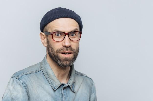 Stijlvolle man van middelbare leeftijd met een verbaasde en nieuwsgierige uitdrukking draagt een bril, een spijkerjasje en een hoed