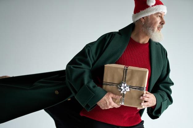 Stijlvolle man van middelbare leeftijd met kerstmuts die een casual outfit draagt, wegkijkend met een geschenkdoos