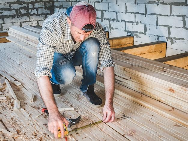 Stijlvolle man, werkt met gereedschap op hout
