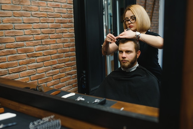 Stijlvolle man zit kapper haarstylist kapper vrouw knippen zijn haar