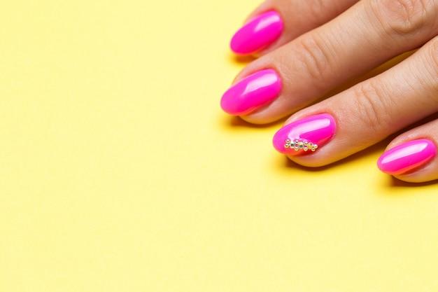 Stijlvolle manicure roze op een geel.