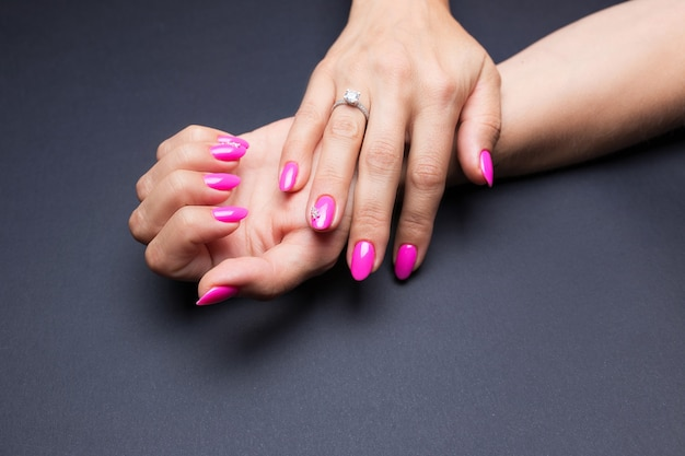 Stijlvolle manicure roze op een zwarte achtergrond