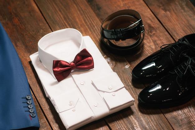 Stijlvolle mannelijke set kleren. overhemd strikje lederen schoenen riem.