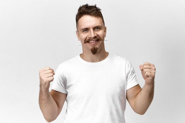 Stijlvolle mannelijke winnaar verheugt zich over zijn overwinning, opgewonden glimlachend naar de camera. bebaarde hipster man met snor balde vuisten, dolblij met succes. triomf, vreugde, winnen en kampioenschap
