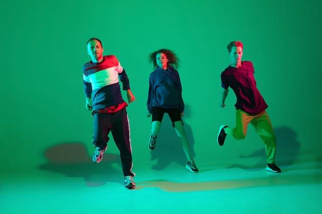 Stijlvolle mannen en vrouwen dansen hiphop in lichte kleding op groene achtergrond in de danszaal in neonlicht. jeugdcultuur, beweging, stijl en mode, actie. modieus portret.