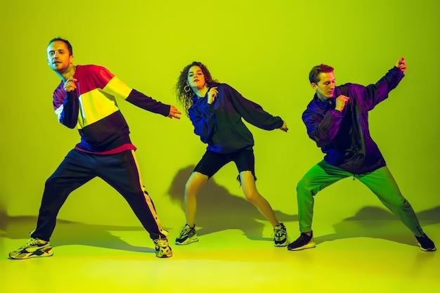 Stijlvolle mannen en vrouwen die hiphop dansen in lichte kleding op een gradiëntachtergrond in de danszaal in neonlicht. jeugdcultuur, beweging, stijl en mode, actie. modieus portret.