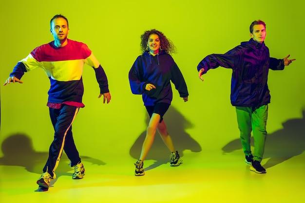 Stijlvolle mannen en vrouwen hiphop dansen in lichte kleding op groene achtergrond in dance hall