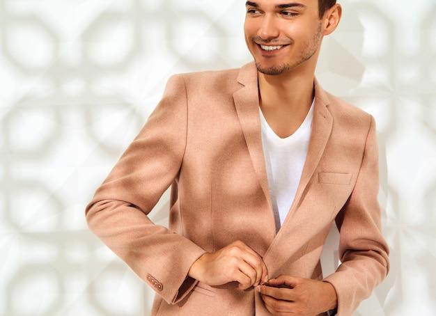 Stijlvolle mannequin gekleed in elegante licht roze pak poseren in de buurt van witte muur