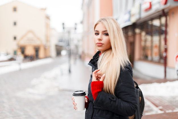 Stijlvolle mannequin vrouw met koffie in een mode-winterjas met een tas wandelen in de stad