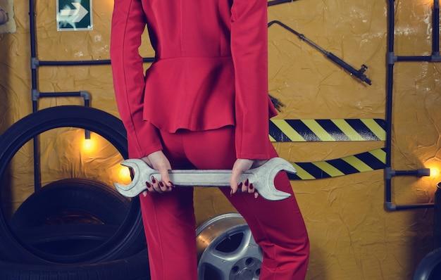Stijlvolle mechanische vrouw in trendy kleding houdt een sleutel