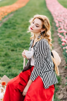 Stijlvolle meisje houdt van kopje thee en picknick in tulpenveld