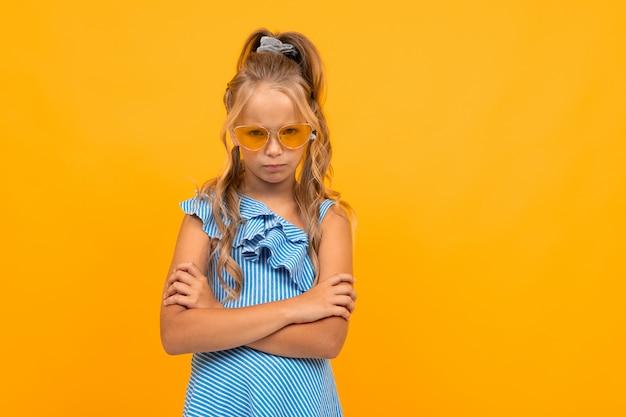 Stijlvolle meisje in een jurk in heldere glazen stak haar armen over een oranje muur
