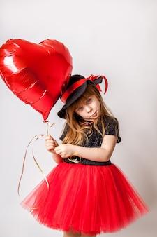 Stijlvolle meisje in jurk en hoed met rode hartvormige ballon