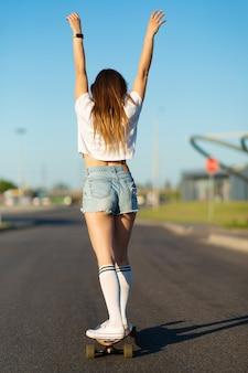 Stijlvolle meisje in witte kousen geniet van rit op longboard opgestoken handen