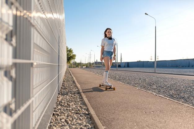 Stijlvolle meisje in witte kousen rijden op longboard in de straat en luisteren muziek