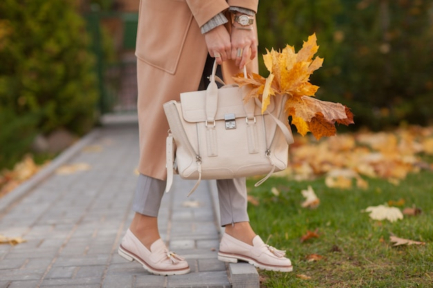 Stijlvolle meisje loopt in herfst park in een beige jas en hoed