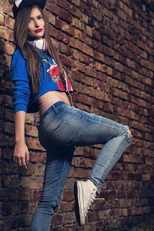 Stijlvolle meisje poseren in de buurt van een bakstenen muur