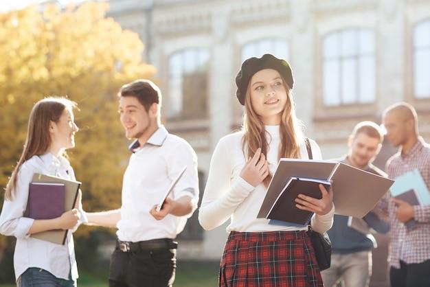 Stijlvolle meisje staat op de binnenplaats van de universiteit.