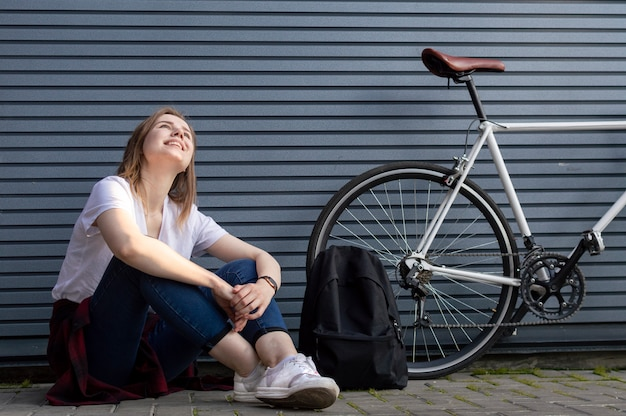Stijlvolle meisje zit in de buurt van de fiets en rugzak en dromen, glimlacht tegen de grijze muur