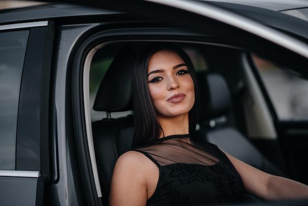 Stijlvolle meisje zit in een business class auto in een zwarte jurk. zakelijke mode en stijl