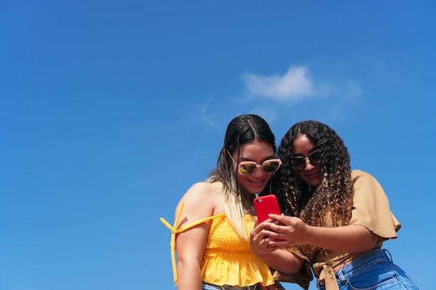 Stijlvolle meisjes die hun mobiele telefoon in de stad controleren. vriendinnen die samen plezier hebben