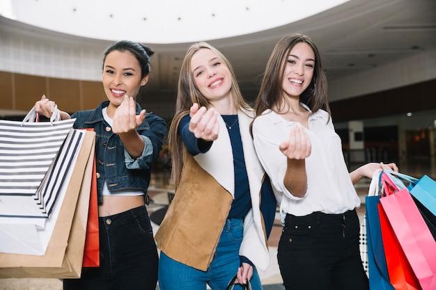 Stijlvolle meisjes gebaren bij camera met zakken