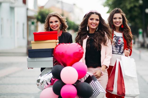Stijlvolle meisjes met boodschappentassen, schoenendozen en luchtballonnen in de stad.