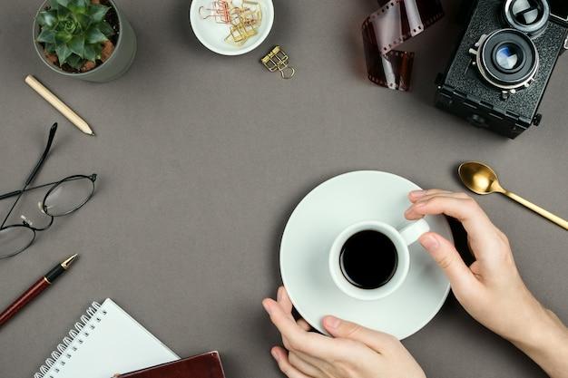 Stijlvolle minimalistische mockup met notebook, planner, bril, vintage camera en vrouw handen met kopje koffie op grijze achtergrond op copyspace