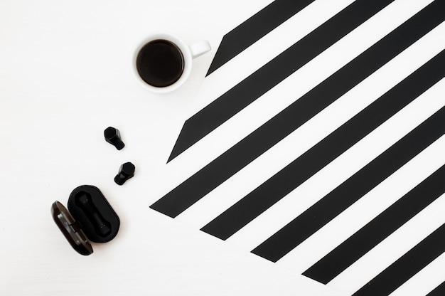 Stijlvolle minimalistische werkruimte met kop koffie, draadloze oortelefoons
