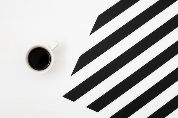 Stijlvolle minimalistische werkruimte met kopje koffie op gestreepte achtergrond