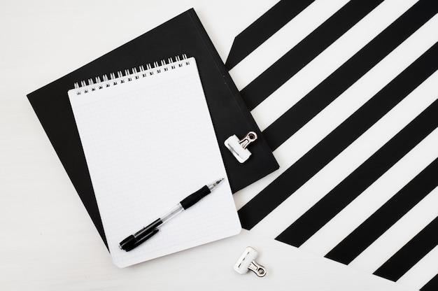 Stijlvolle minimalistische werkruimte met notitieblokmock-up, potlood op gestreepte zwart-witte achtergrond