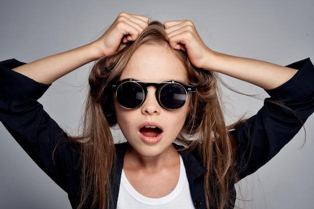 Stijlvolle mode-afbeelding van een klein meisje in zwarte glazen