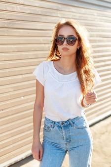 Stijlvolle moderne jonge hipster vrouw in modieuze zonnebril in wit t-shirt in trendy spijkerbroek staat in de buurt van een houten vintage muur op een zonnige warme dag