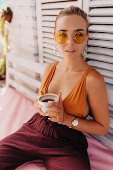 Stijlvolle moderne vrouw in ronde oranje bril en t-shirt buiten zitten op zomerterras met koffie