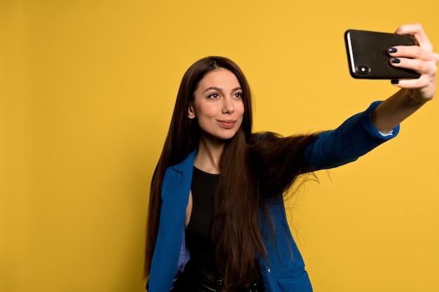 Stijlvolle moderne vrouw met lang donker haar dragen blauwe jas selfie met smartphone maken