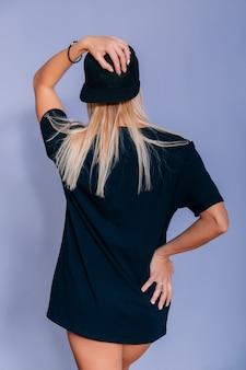 Stijlvolle modieuze blonde meisje met pet in zwarte kleding. grijze achtergrond, niet geïsoleerd