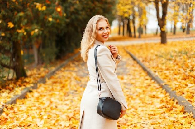 Stijlvolle modieuze jonge vrouw in een klassieke jas met een tas poseren in de buurt van een boom met geel blad