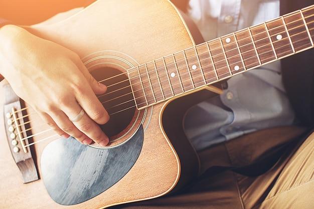 Stijlvolle, modieuze man in een blauw shirt, donkerblauwe jas en bruine broek gitaar spelen. de concepten van hobby, passie en interesse in muziek. de handenkerel raakt de koorden van de gitaar, close-up.