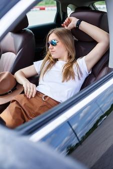 Stijlvolle modieuze mooi meisje zit in de salon van een zwarte business class auto. jonge vrouw met een glimlach op haar gezicht. vrouw op een parkeerplaats