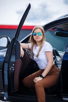 Stijlvolle modieuze mooi meisje zit in de salon van een zwarte business class auto. jonge vrouw met een glimlach op haar gezicht.
