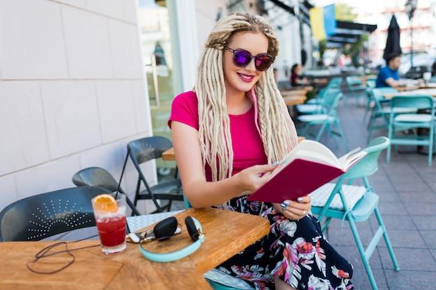 Stijlvolle modieuze vrouw met witte dreadlocks in zonnebril bedrijf notebook en haar vrije tijd doorbrengen in modern restaurant. verse smoothie en oortelefoons op tafel.