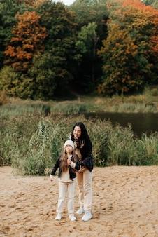 Stijlvolle moeder en dochter in leren jassen blazen bellen in een herfstpark