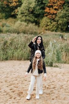 Stijlvolle moeder en dochter in zwarte leren jassen blazen bellen op het zand