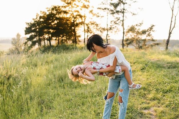 Stijlvolle moeder en knappe dochter met plezier op de natuur. gelukkig gezin concept. schoonheid natuurscène met familie buitenlevensstijl. familie samen rusten. geluk in het gezinsleven. moederdag
