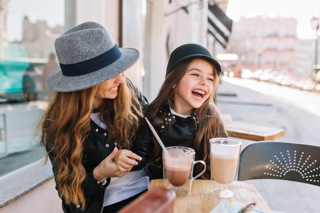 Stijlvolle moeder en vrij lachende dochter genieten van weekend samen in openluchtrestaurant koffie en milkshake drinken.
