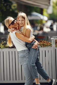 Stijlvolle moeder met dochter in een zomerstad