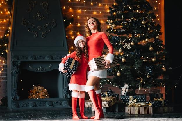 Stijlvolle moeder met dochtertje in kerstkostuums in de buurt van de kerstboom. vrolijk kerstfeest.
