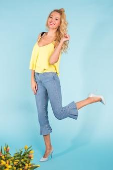 Stijlvolle mooie blonde jonge vrouw die zich voordeed op blauwe muur
